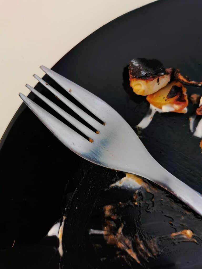 Tom tallrik med lite matrester och en gaffel