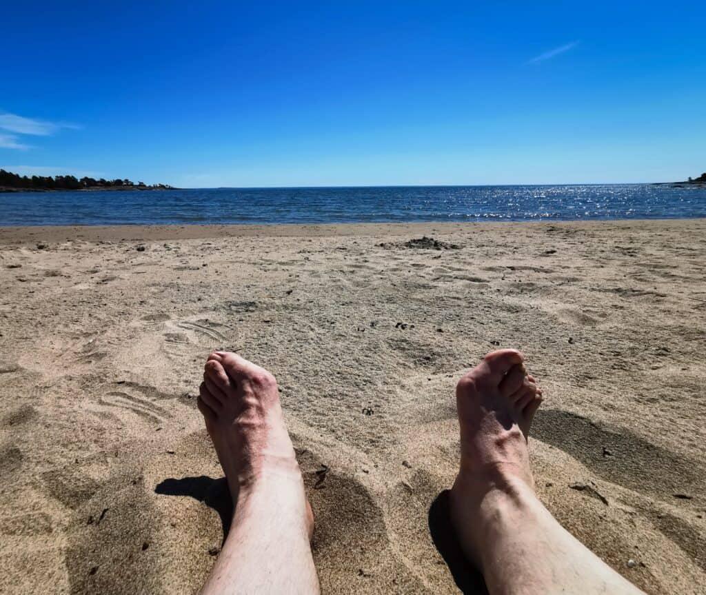 Bara ben och fötter på en sandstrand på Degersands strand på Åland.