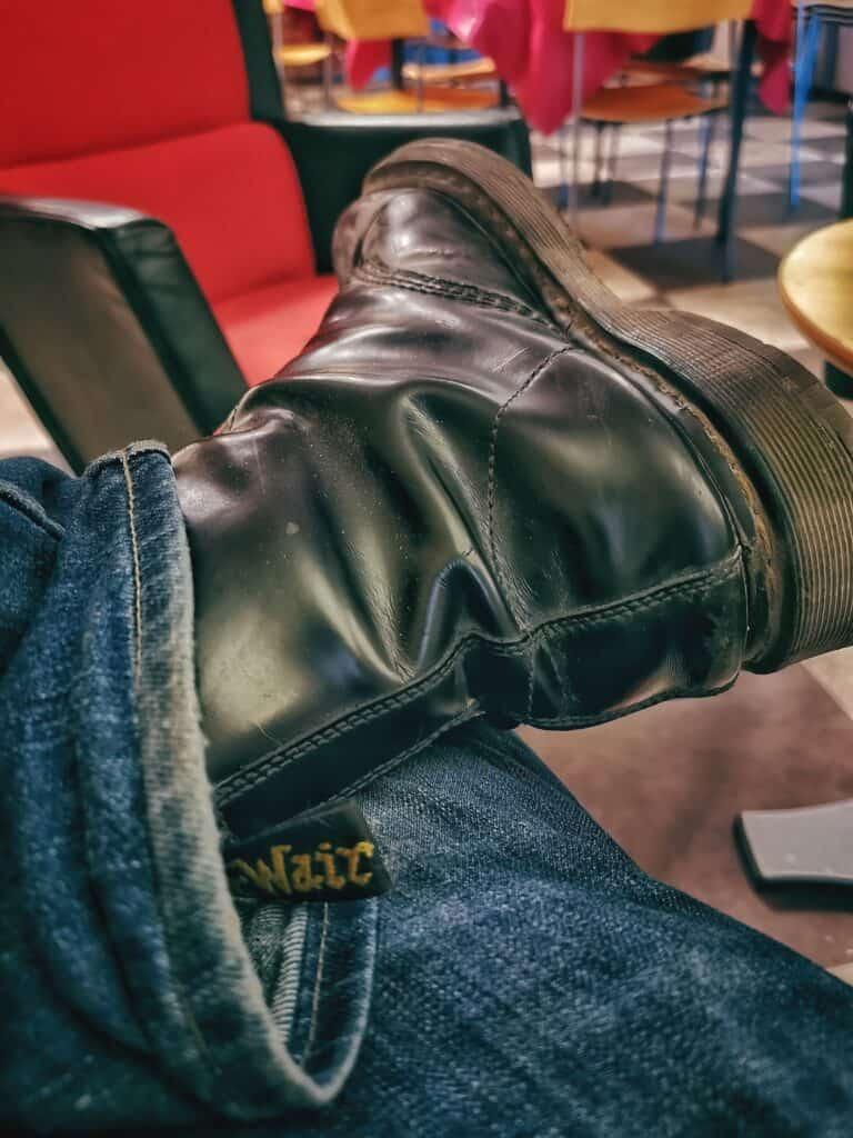 Rast i reklamfabriken i Köping. Ett par slitna Doc Martens hänger på ett jeansbeklätt knä.