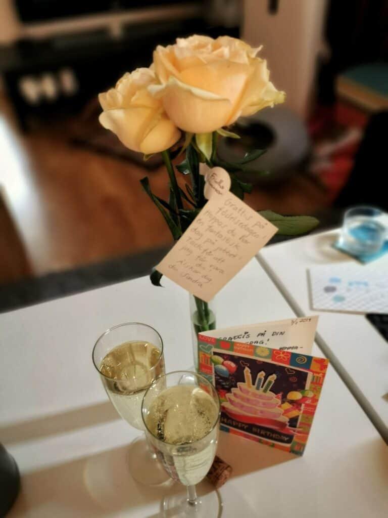 En bukett rosor och två glas bubbel tillsammans med ett gratulationskort.